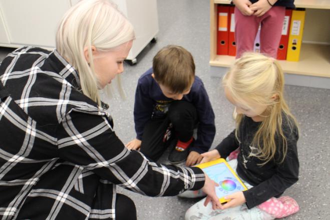 Lukiolainen opastaa kahta eskari-ikäistä iPadin äärellä.