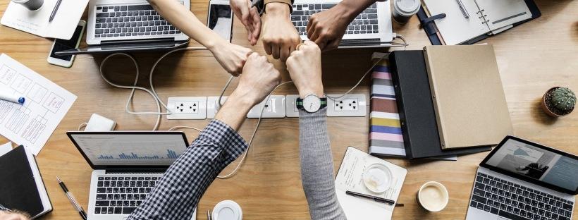Viisi kättä työpöydän yllä nyrkit vastakkain yhteistyön merkiksi